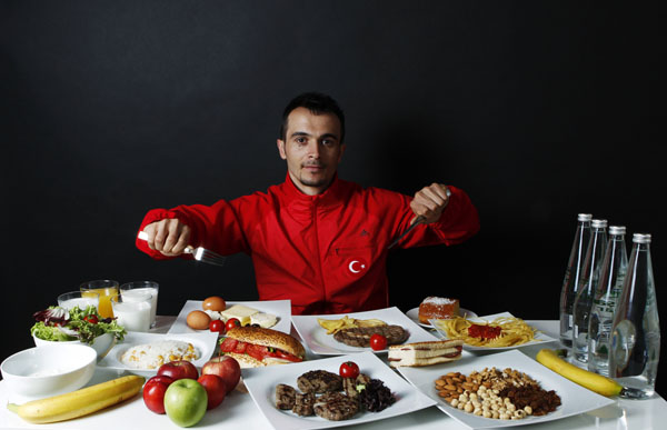 Turkish weightlifter and Olympic hopeful Mete Binay poses in front of his daily meal intake in Ankara