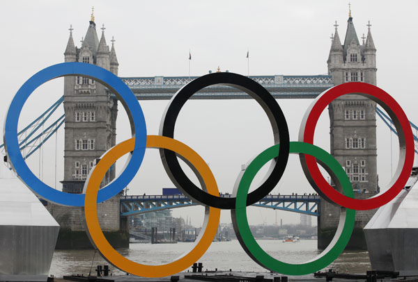 Olympic rings, mounted on a barge, are positioned in front of Tower Bridge on the River Thames in London